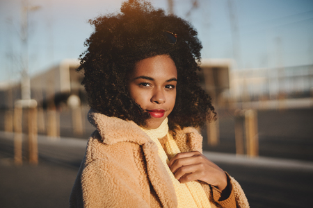 An outdoor portrait of a young beautiful Brazilian girl in a warm casual outfit and with curly afro hair standing on evening street and looking at the camera, winder sunset in Lisbon, Portugal
