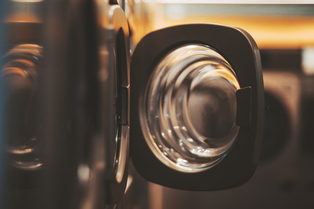 A dark yellowish room of a publiс laundry with a row of washing machines, selective focus on the opened door of one of the tumble dryers, shallow depth of field Stock Photo