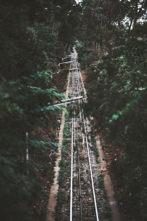 A dark atmospheric railroad track in an alley of greenery stretching into the distance; a beautiful dark corridor with a funicular railway track on the mountain with the row of modern lantern poles Stock Photo