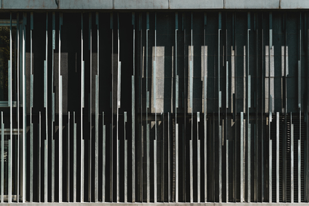 A frontal view of an abstract metal contemporary building facade with striped iron vertical blocks of different form and thickness; view of an outdoor exterior of a modern house with an odd texture 免版税图像
