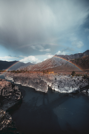 Amazing wide-angle vertical landscape with a stunning double rainbow stretched over two banks of a mountain river Katun during autumn rain through sunshine with ridges behind and rocky cliff in front
