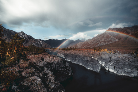 A stunning double rainbow stretched over two riverbanks of a Katun river in mountains of Altai during the autumn: rocky cliff, ridges overgrown with native grasses, and a dramatic stormy sky behind Banque d'images