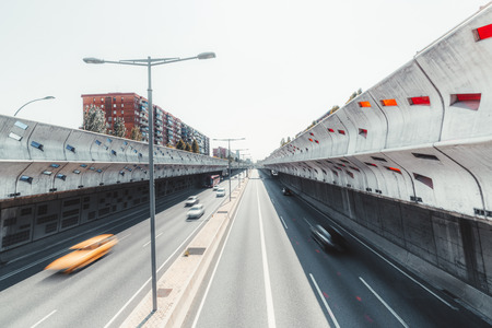 A modern highway in recess stretching into vanishing point, in the center of Barcelona, Spain, with concrete soundproof walls, long exposure, multiple motion blurry cars and the bus, sunny summer day