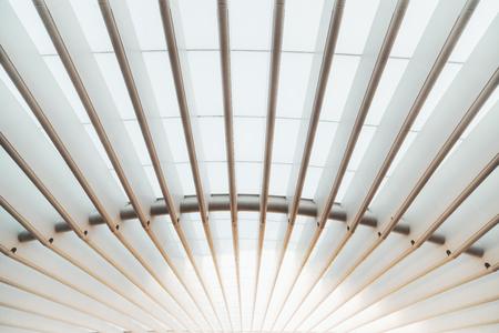 Szerokokątny widok białej konstrukcji dachu na zewnątrz nowoczesnego budynku wykonanej z równoległych grubych pustych żelaznych dźwigarów i półprzezroczystego pokrycia, które przepuszcza i rozprasza światło słoneczne