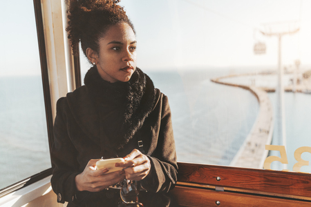 A charming young African-American tourist female is enjoying sightseen while sitting inside of a ropeway cabin and pensively looking aside, with a copy space place on the right for your advert info