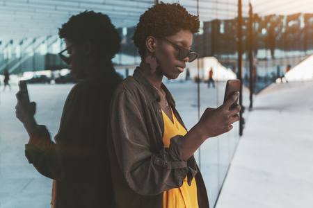 Young fancy African female is using her smartphone to talk with a colleague while leaning against the glass wall of the facade of a modern business building outdoors which fully reflects her
