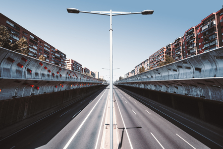 An empty modern highway in recess stretching into the vanishing point, going through a residential district of Barcelona, Spain, with concrete soundproof walls, central perspective, warm sunny day