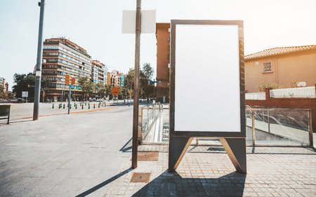 A white blank advert poster placeholder in urban settings; a vertical empty information billboard mockup next to metro entrance; a template of a city signboard near the road in a residential district