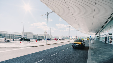 Cabstand in front of the entrance of modern airport in Barcelona, cab rank with several taxis near glass facade of a contemporary airport terminal in Spain with the road, huge ceiling and parking lot