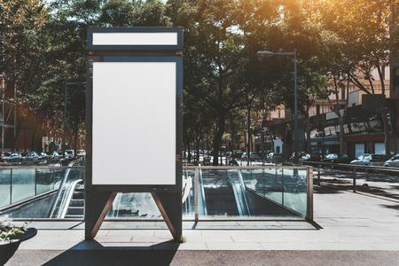 Mockup eines leeren vertikalen Plakats der Außenwerbung in der Nähe eines unterirdischen Eingangs; Vorlage eines vertikalen Informationsbanners auf der Straße in der Nähe einer U-Bahn; ein leerer weißer Platzhalter für Anzeigen in städtischen Umgebungen