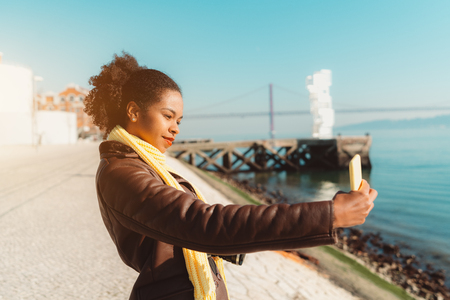 A dazzling young African-American tourist woman is taking a smartphone selfie on the riverside, warm spring day; charming Brazilian girl is photographing herself on cellphone on the quay of a river Imagens
