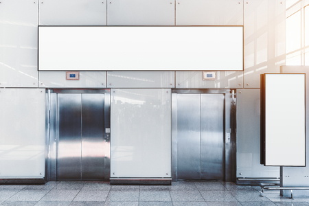 Two modern elevators in an airport terminal or a shopping mall or a railway station depot with two blank mockups: placeholder above and on the right, for your advertising or information text message