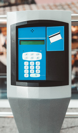 A vertical modern electronic desk with an intercom for card payment; an outdoor parking payment terminal with numeric keypad, bank card reader area, speaker, and a small liquid crystal display