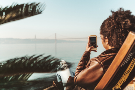 Wide-angle side view of a curly-hair woman enjoying the sunset while sitting on the daybed outdoors on a riverside and shooting a bridge in the background using a camera of her modern smartphone