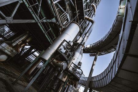Wide-angle view from the ground of a contemporary oil refinery or a modern fuel factory facility in an industrial zone, with two round bridges, plenty of pipes, metal beams, tanks, and stairs Stok Fotoğraf