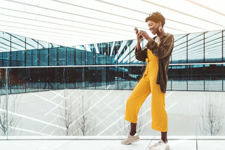 A young African fancy businesswoman in yellow overalls is standing in front of a glass fence of a modern business office building while messaging via her smartphone, a copy space area on the left Stockfoto