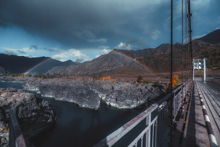 An incredible double rainbow over the mountain river Katun in Altai mountains with a metal suspension bridge over the water on the right, rocky coast, hill ridge in the background, partly storm clouds