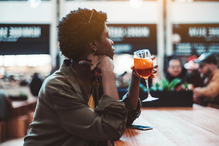 A thoughtful young fancy black female with a short Afro hair is drinking cocktail indoors; a pensive charming African girl with a glass of delicious spritz aperol drink is thoughtfully looking aside