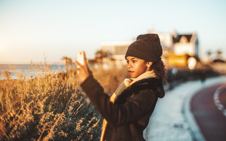 True tilt-shift portrait of a dazzling African-American girl in a warm demi-season coat and hat photographing an amazing sunset outdoors near the waterfront lit by the evening sun, Cascais, Portugal Stock Photo