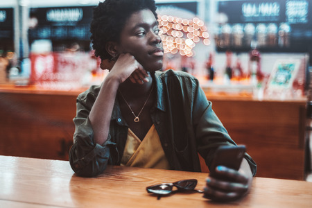 A thoughtful young African woman with short afro hair is pensively looking aside while sitting indoors of a bar or a cafe, waiting for her order, and holding the smartphone in hand Archivio Fotografico