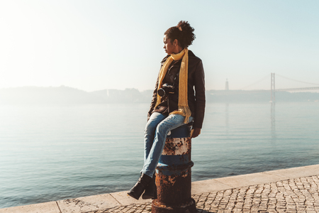 African-American tourist girl in demi-season clothes is sitting on a bollard on the embankment and looking aside with a suspension bridge in the background, a warm sunny day in Lisbon, Portugal