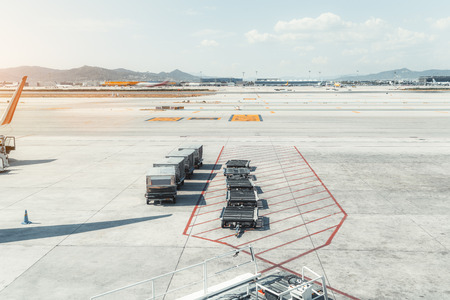 View of machinery on the boarding area of a contemporary airport terminal El Prat in Barcelona, with four containers with a mealand empty connected baggage carts, take-off field in the background