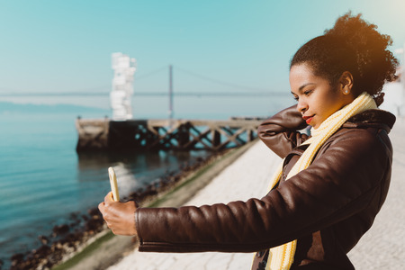 A gorgeous young African-American woman in a coat is taking a selfie while standing on the embankment of the river with her smartphone, a huge suspension bridge in the background, Lisbon, Portugal