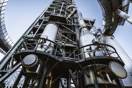 Wide-angle view from the bottom of a contemporary building of oil refinery or a modern fuel factory facility in an industrial zone, with a round bridge, plenty of pipes, metal beams, tanks, and stairs Stock fotó