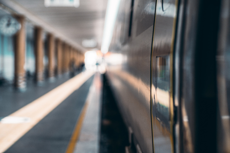 View with a very shallow depth of field of a high-speed suburban train and the platform of a railway station depot with a row of columns stretching into the distance, selective focus on a door line Zdjęcie Seryjne - 122460756