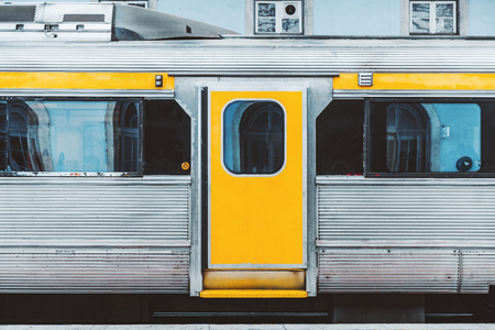 A typical European suburban train waiting on the platform in Portugal; the area of the door in the middle of the wagon of an old-fashioned high-speed train with aluminum plating with yellow areas Zdjęcie Seryjne