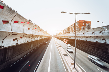 Wide-angle long exposure view from of a modern highway in Europe stretching into the distance and protected with soundproof concrete walls with colored holes, street lights in the center, Barcelona