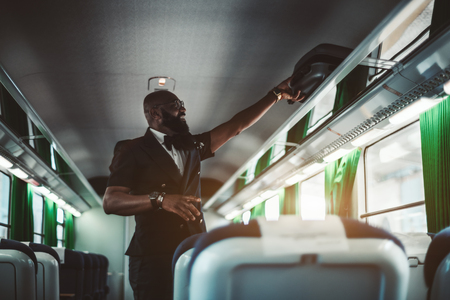 A fancy African businessman is putting his travel bag on the shelf indoors of a modern high-speed train; a bearded black man entrepreneur is picking his suitcase before leaving the suburban train