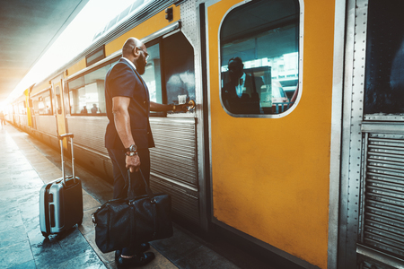 Wide-angle view of an elegant bearded bald African male entrepreneur standing on the railway station platform and pushing the button to open the door of a high-speed train to start a business trip