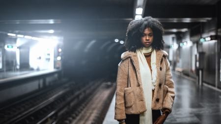 A dazzling African-American girl with curly lush Afro hair in a demo-season coat and scarf is standing on the subway platform waiting for the train; cute biracial female in the metro