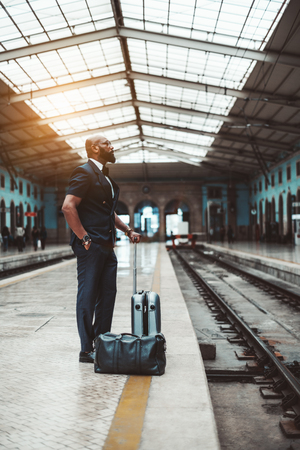 A fancy black guy with travel bags is waiting for his train on the platform of a railway station depot; vertical shot of an African businessman waiting for the train for his business trip indoors Zdjęcie Seryjne