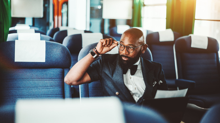 Portrait of an adult bald fashion African businessman with beard looking out the window adjusting his eyeglasses while sitting indoors of the first-class car of a high-speed train Stok Fotoğraf