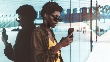 A charming fancy black girl in sunglasses and with earrings in the shape of Africa is messaging via smartphone outdoors; a fashion young black female is taking a selfie using her cellphone on a street
