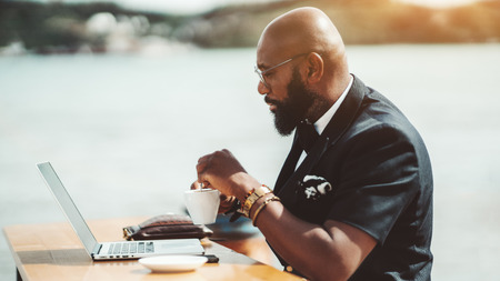 A pensive adult bald bearded African guy in a vest and eyeglasses is reading a news feed on the screen of his laptop while sitting in an outdoor cafe with a river in the background and drinking coffee