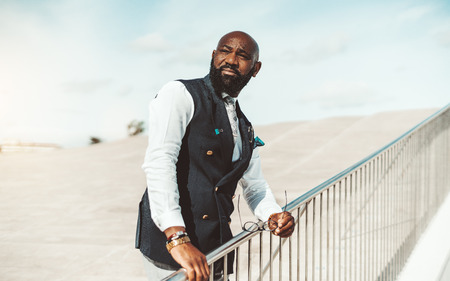 Portrait of a serious noble bald bearded African man in an elegant vest standing outdoors with the spectacles in a hand, holding a chromium-plated bridge fence and squinting looking aside