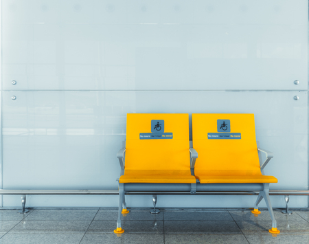 Doubled yellow plastic seats for disabled indoors in front of a glass wall with