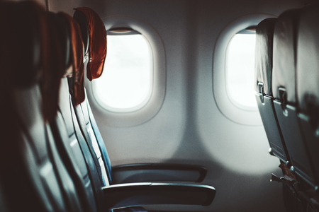 A dark aircraft interior: the row of modern empty leather seats with armrests down, shallow depth of field, selective focus on the closest seat to the porthole, red rag mat under the head Stok Fotoğraf
