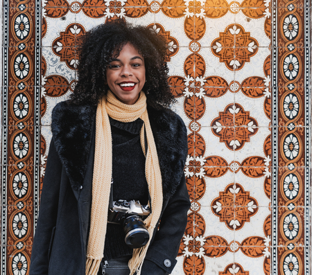 A dazzling laughing African-American female tourist with curly Afro hair and in a black coat and scarf, with a vintage film camera in front of a wall made of traditional Portuguese Azulejo tiles