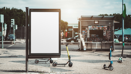 Mockup of an empty urban advert poster surrounded by scooters scattered across the street on the pavement stone; template of a blank street information billboard with a newsstand in the background Stok Fotoğraf