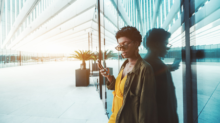 A charming African businesswoman in eyeglasses near the glass wall outdoors is using her smartphone; a young black female entrepreneur with the cellphone in an outdoor area of her business office