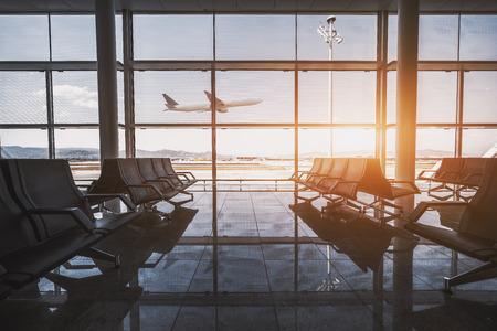 Weitwinkelansicht eines modernen Flugzeugs, das die Höhe außerhalb der Glasfensterfassade einer zeitgenössischen Wartehalle mit mehreren Sitzreihen und Reflexionen im Inneren eines Flughafenterminals gewinnt Standard-Bild