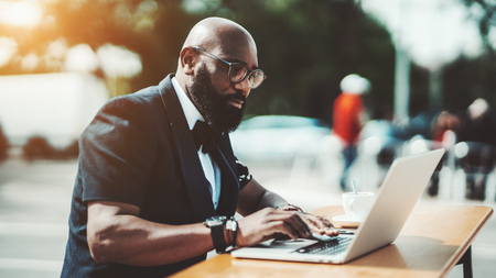 A strong adult bold African man entrepreneur in eyeglasses is working on the laptop in an outdoor cafe; a bearded businessman in a street bar with his netbook and a cup of delicious coffee