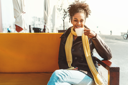 A Dazzling young happy African-American female is drinking a delicious coffee drink in an outdoor bar; smiling Brazilian girl in demi-season coat and scarf is drinking tea in a cafe outdoors Stok Fotoğraf