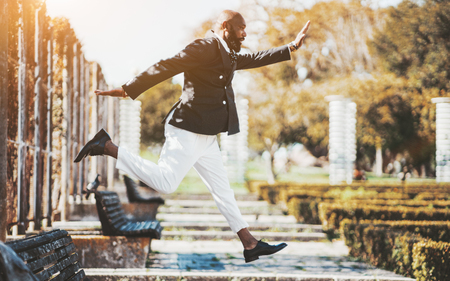 Side view of a fancy bald bearded black guy in an elegant suit is jumping high in the park; a fashionable African man entrepreneur is fooling around and makes a jump in a pose in a public park Stok Fotoğraf