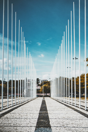 Vertical view of a long symmetrical alleyway framed with two rows of white empty flagpoles on sides casting regular shadows on pavement stone with a black line in the center, Lisbon, Portugal Stok Fotoğraf