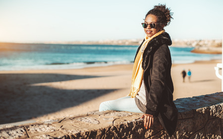 A happy young African-American female in sunglasses and coat is sitting on the stone fence wall on a sunny day with beach and water in the background and a copy space area on the left for your ad text